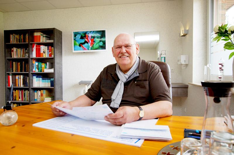 Migräne Heilpraktiker Heino Nieland sitzt am Schreibtisch